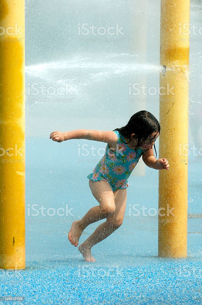 Girl playing in water sprinkler royalty-free stock photo