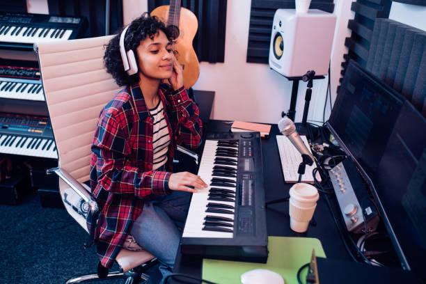 Girl playing keyboards and recording music in the studio stock photo