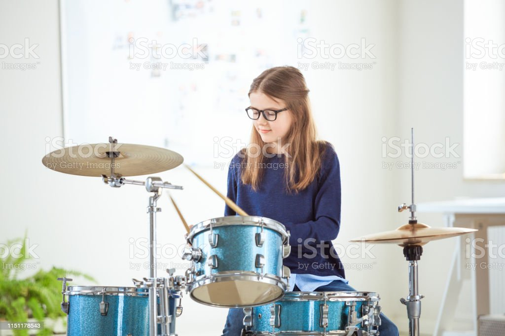 Girl playing music on drums at training class Pre-adolescent girl playing music on drums at training class. Confident female student is practicing at conservatory. She is casuals at education building. 10-11 Years Stock Photo