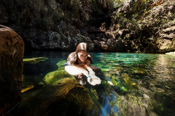 Girl playing on a pond A DSLR Canon photo of a 10 year old Brazilian girl inside a clear water small pond trying to catch some fishes with her hand. Chapada dos Veadeiros (Veadeiros Plateau), Goiás, Brazil. goias stock pictures, royalty-free photos & images