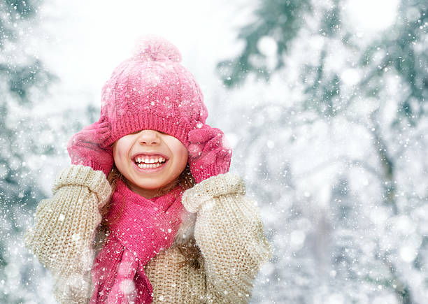 girl playing on a winter walk - warm clothing stock photos and pictures