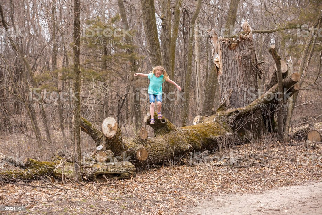Girl Playing on Fallen Tree in Woods foto stock royalty-free