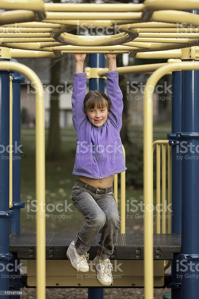 Girl Playing on Monkey Bars stock photo