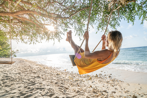 Young woman swinging on beach by the sea, beautiful and idyllic landscape. People travel vacations concept.
