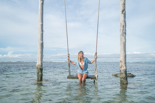 Young woman swinging over the sea, beautiful and idyllic landscape. People travel vacations concept.
