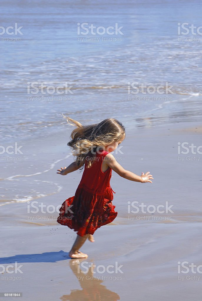 Girl playing on the beach stock photo
