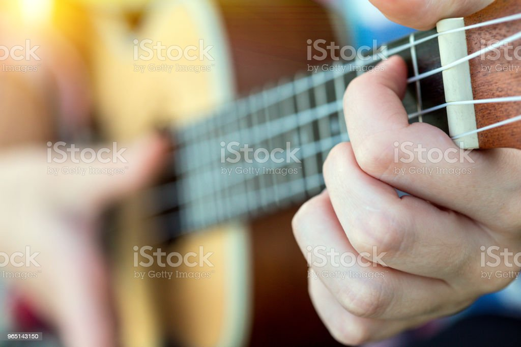 girl playing on ukulele. hands playing a guitar close-up royalty-free stock photo