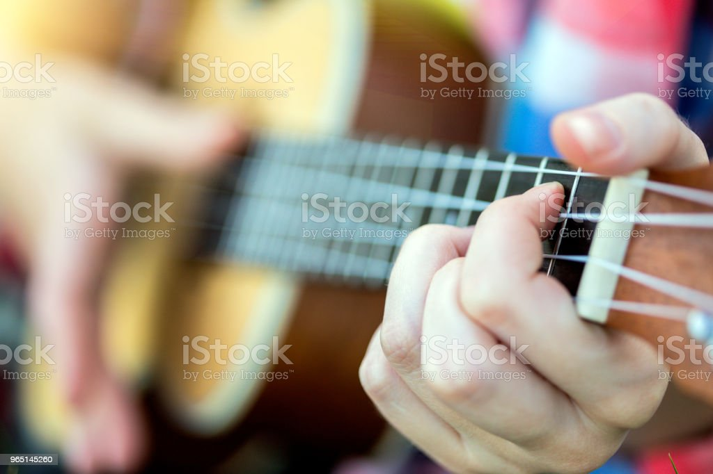 girl playing on ukulele. hands playing a guitar close-up zbiór zdjęć royalty-free