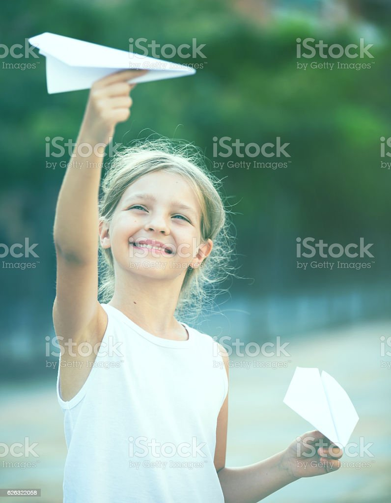 girl playing paper airplanes stock photo