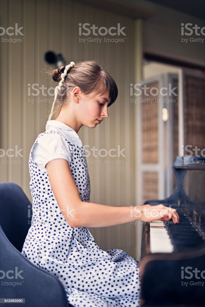 Teenage girl playing concert on an old grand piano.