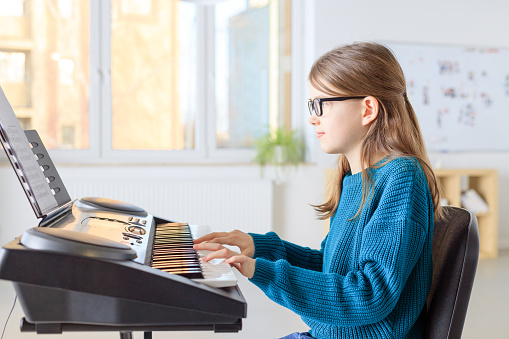 Girl Playing Piano In Music Class Stock Photo - Download Image Now