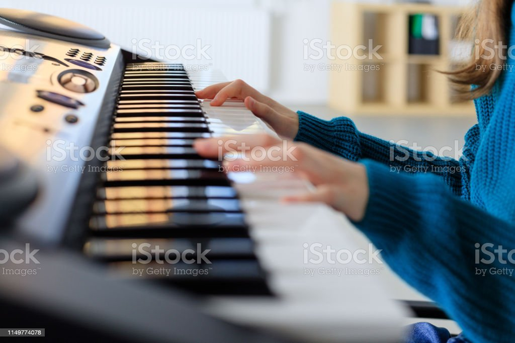 Girl playing piano in training class Midsection of girl playing piano. Female student is learning on keyboard instrument. She is sitting in music class. 10-11 Years Stock Photo