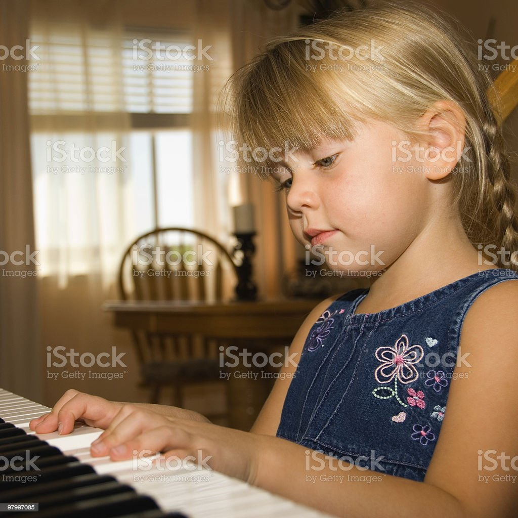 Girl playing piano royalty free stockfoto