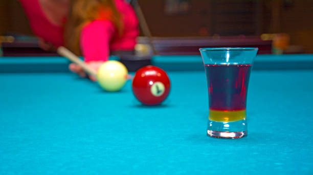 girl playing pool, has the ball and is reflected in the glass - target australia stock pictures, royalty-free photos & images