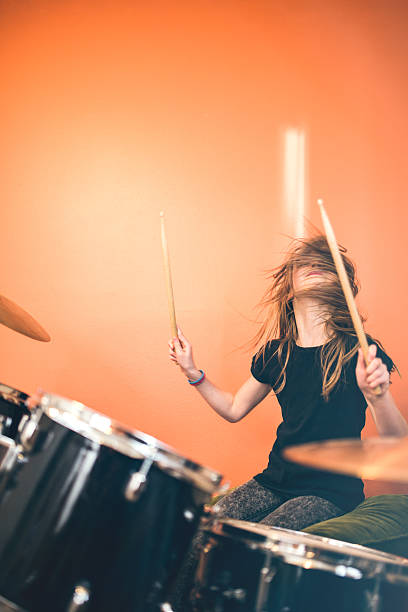 Girl Playing Rock and Roll Drums A 9 year old girl has fun playing a drum set in her room, working on songs for her band.  Bright sunlit bedroom with orange walls. drummer stock pictures, royalty-free photos & images
