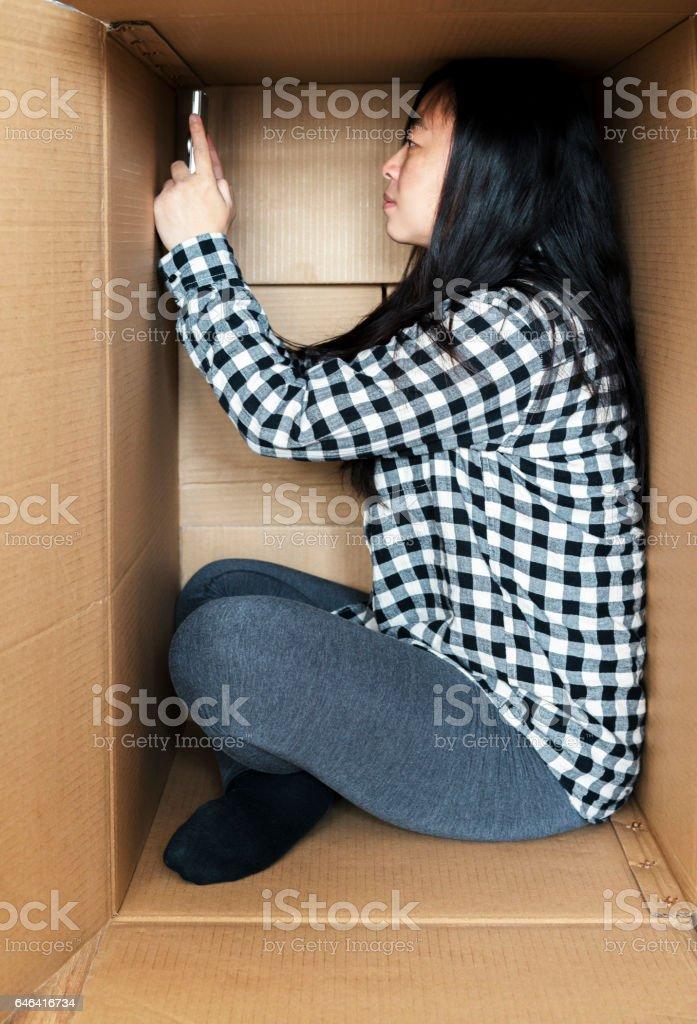 girl playing smartphone in cardboard box stock photo