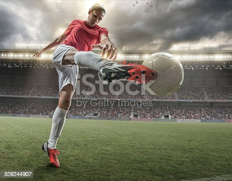 A close up image of woman soccer player kicking ball in a outdoor floodlit stadium full of spectators under a stormy evening sky. The player is wearing generic red and white unbranded football kit. The stadium is generic, created in Photoshop with fake advertising. Composite image with intentional lighting effects.