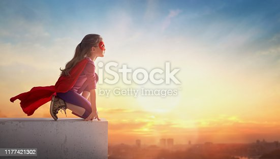 Little child girl playing superhero. Child on the background of sunset sky. Girl power concept