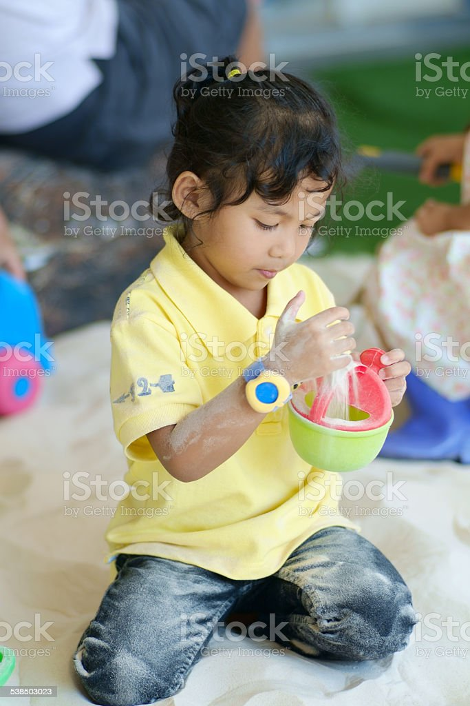 Girl playing the indoor sand playground stock photo