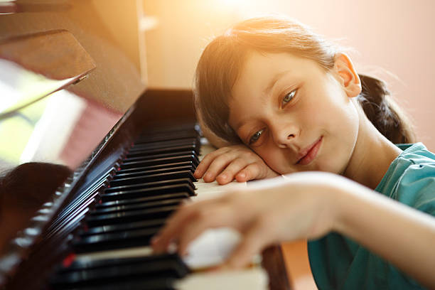 mädchen spielen klavier - lautbildungsspiele stock-fotos und bilder