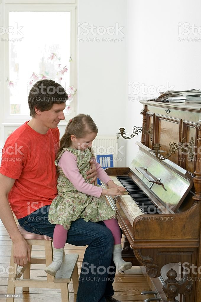 Girl playing the piano with her father royalty-free stock photo
