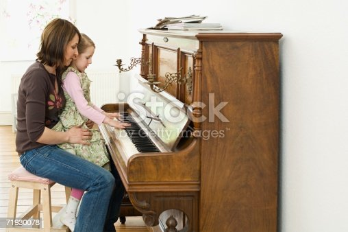 istock Girl playing the piano with her mother 71930078