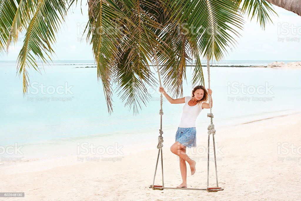 Girl playing the swing on beach stock photo