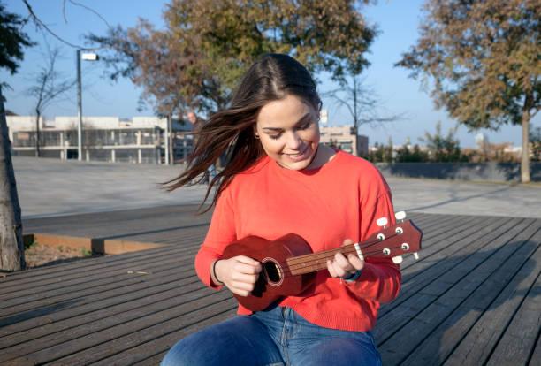 mädchen spielen ukelele im park - ukulele songs stock-fotos und bilder