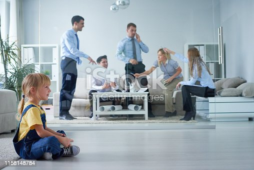 Little girl in casual clothes playing video game and sitting on floor near meeting room during discussion of business project