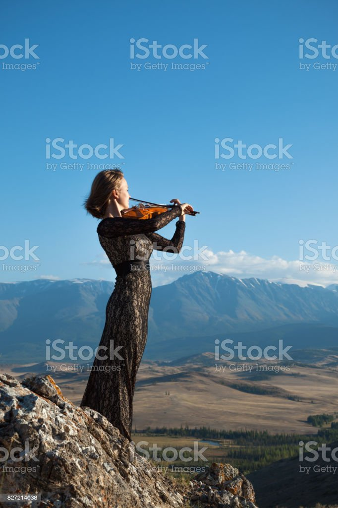 Girl playing violin on nature stock photo