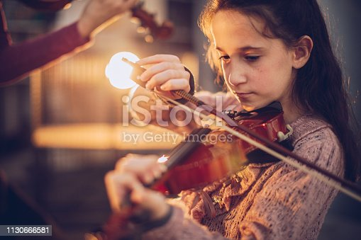 One young girl playing violin.