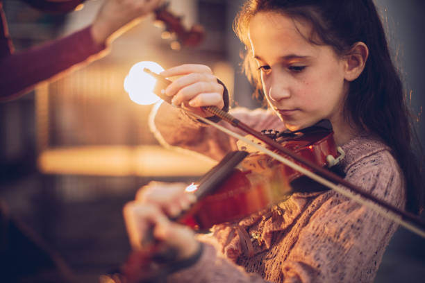 Girl playing violin One young girl playing violin. child prodigy stock pictures, royalty-free photos & images