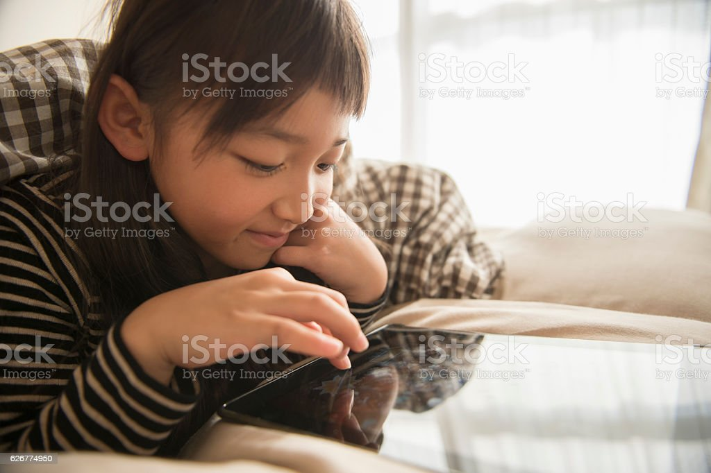 Girl playing with a digital tablet in bedroom stock photo
