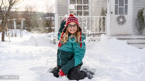 Girl playing with a snow in front of the house, during COVID-19
