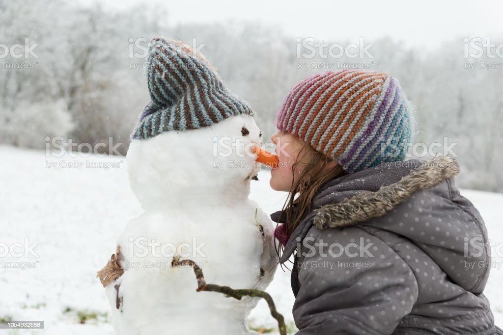 Mädchen spielen mit einem Schneemann - es ist Essen die Karotten-Nase Schneemann – Foto