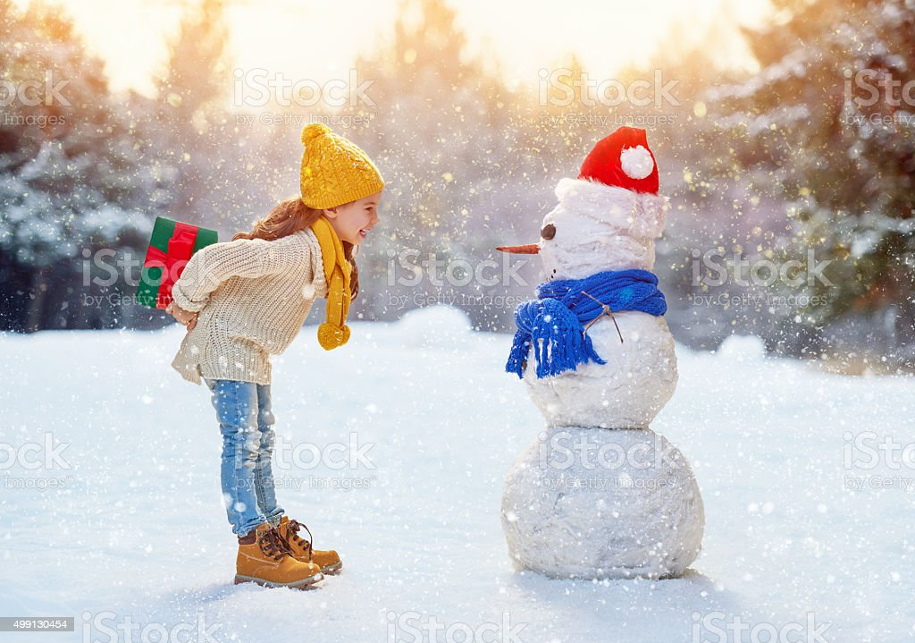 girl playing with a snowman stock photo