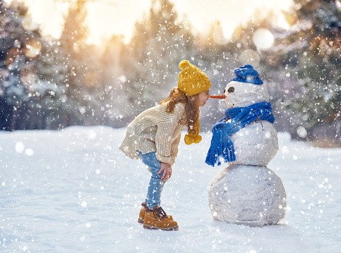 girl playing with a snowman