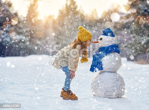 istock girl playing with a snowman 499910260