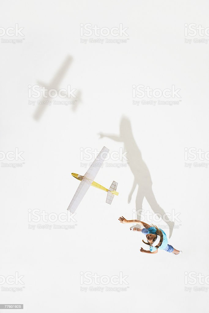 Girl playing with a toy plane stock photo