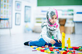A Middle-eastern girl is sitting on the floor in her elementary school classroom. She is playing with blocks, and smiling at the camera while building towers.