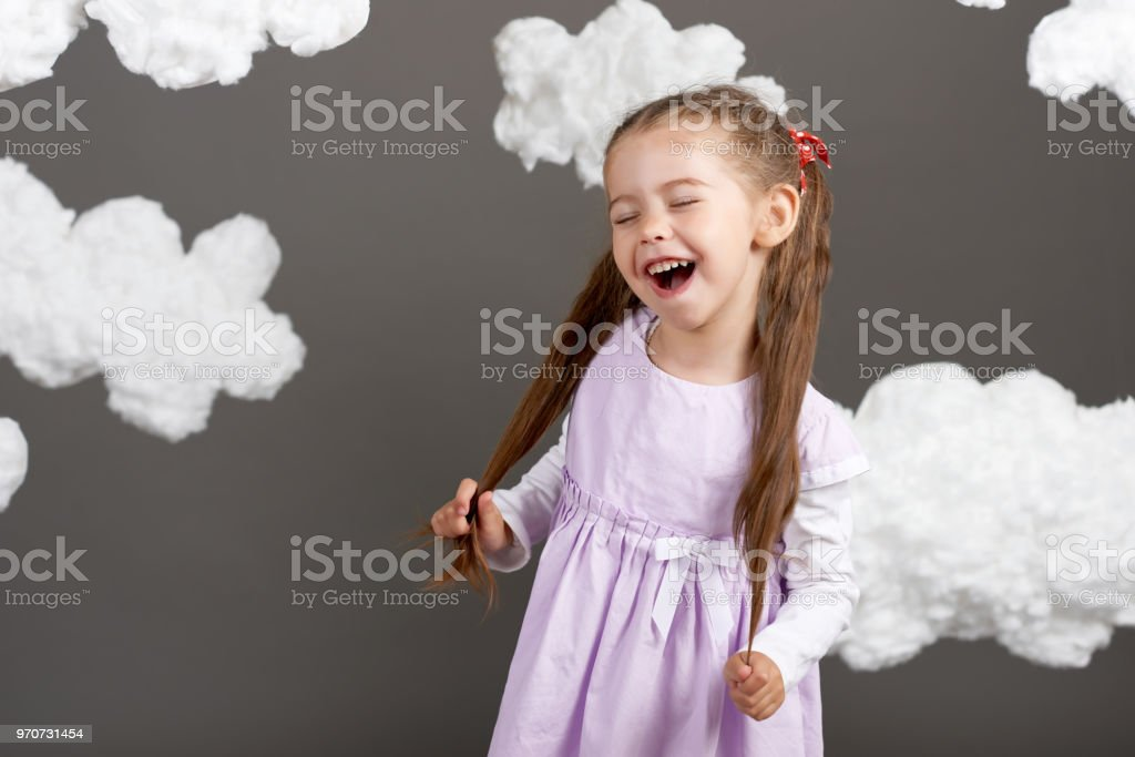 girl playing with clouds, shooting in the studio on a gray background, happy childhood concept stock photo