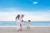 Girl playing with family on the beach. daughter and family happy time