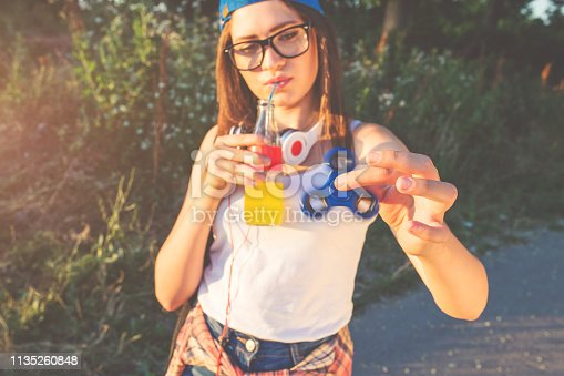 Pretty hipster girl playing with fidget spinner in a park