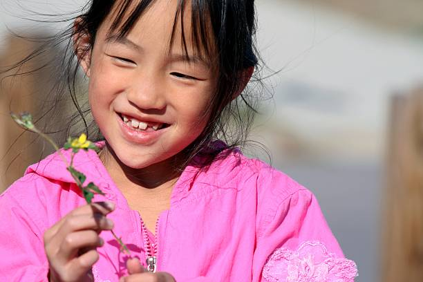 girl playing with flower stock photo