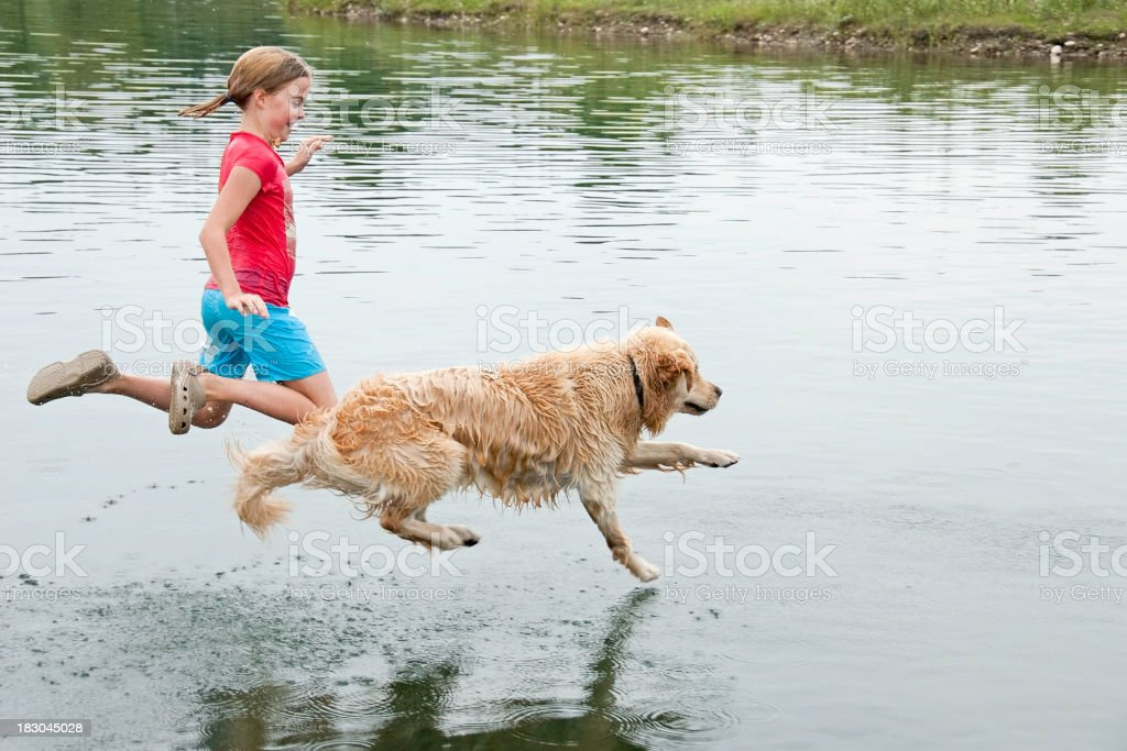 Girl playing with her dog in water stock photo