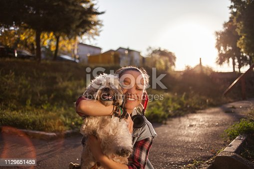 istock Girl playing with her dog 1129651453