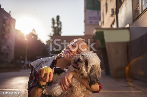 istock Girl playing with her dog 1129651530