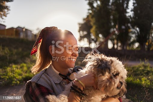 istock Girl playing with her dog 1129651637