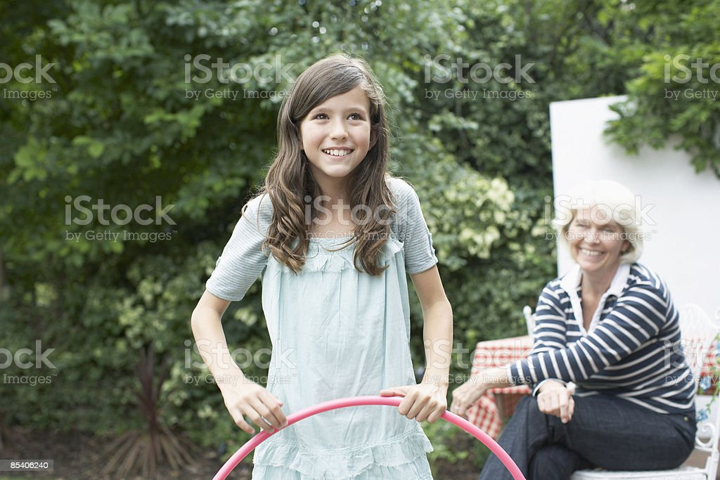 Girl playing with hula hoop in backyard royalty-free stock photo