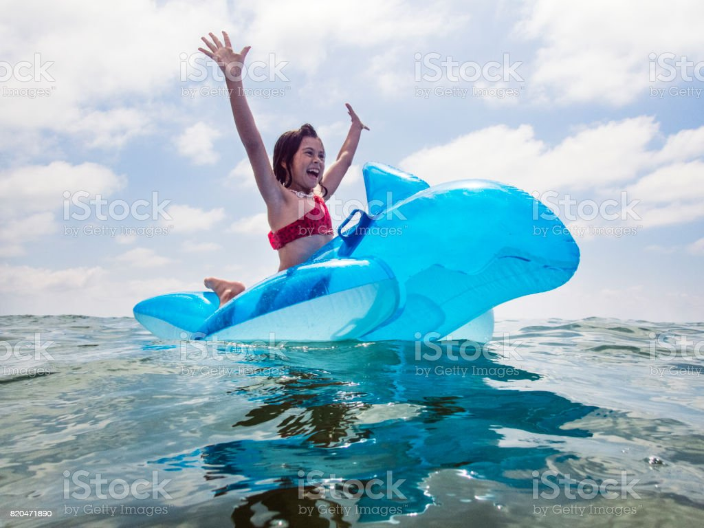 Girl playing with inflatable toy at the sea stock photo